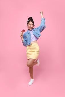 ピンクの背景で隔離の手でクレジットカードを示す幸せな美しいアジアの10代買い物中毒の女性。