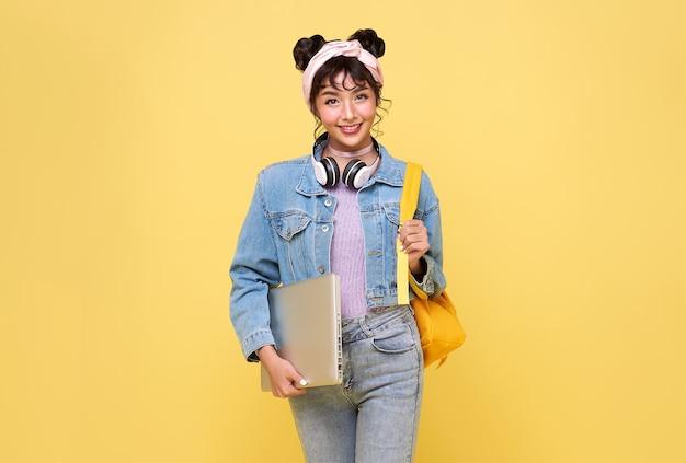 노란색 배경에 격리된 노트북을 들고 배낭을 메고 행복한 아름다운 아시아 10대 학생입니다.