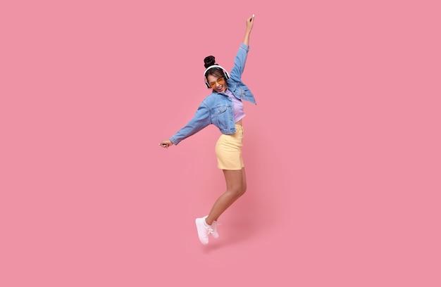 Счастливая красивая азиатская предназначенная для подростков женщина в желтых очках, слушая музыку в наушниках и танцует на розовом фоне.