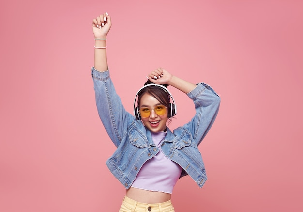 헤드폰에서 음악을 듣고 분홍색 벽에 춤을 노란색 안경에 행복 한 아름 다운 아시아 십 대 여자.