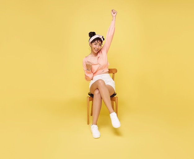 Happy beautiful asian teen woman sitting on chair and hands up celebrating gesture on yellow wall. excited winner success concept.