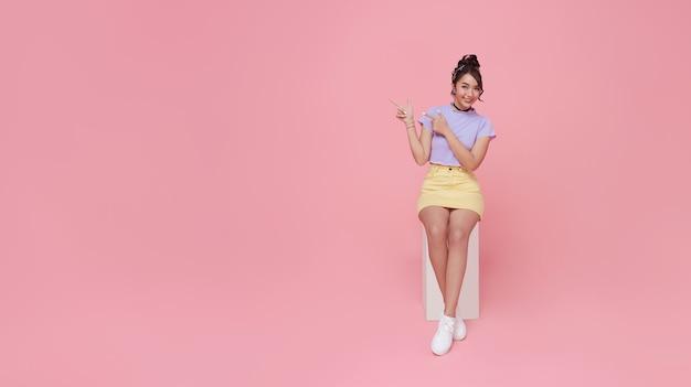 Счастливая красивая азиатская предназначенная для подростков женщина сидя на стуле и руках указывая на розовую предпосылку с космосом экземпляра. панорамный фон.