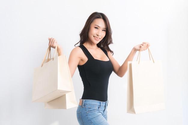 Счастливая красивая азиатская женщина черная длинноволосая женщина в черной рубашке, несущей хозяйственные сумки на сером