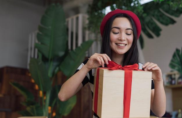 집에서 선물 상자를 여는 행복 한 아름 다운 아시아 여자. 빨간 리본으로 크리스마스 선물을 들고 감정적 인 한국 여성