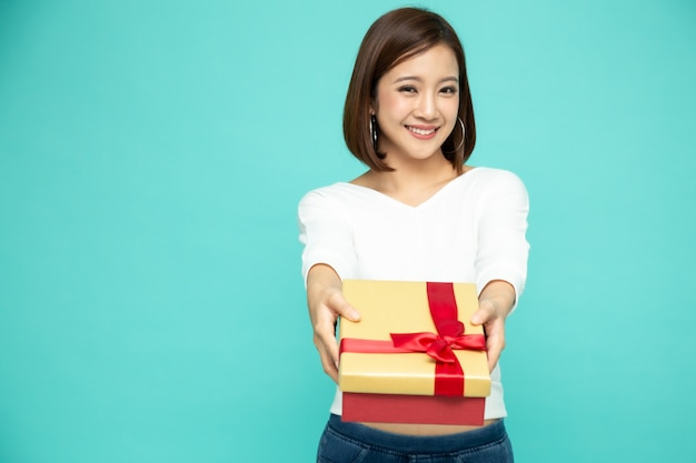 Happy beautiful asian woman smile with gold gift box isolated on green wall. teenage girls in love, receiving gifts from lovers. new year or christmas concept