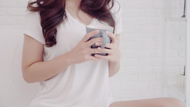 Счастливая красивая азиатская женщина усмехаясь и выпивая чашку кофе или чая на кровати