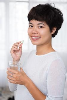 Happy beautiful asian woman taking pill