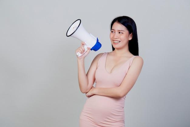 행복 한 아름 다운 아시아 여자 복사 공간 밝은 회색 표면에 고립 된 magaphone에 얘기