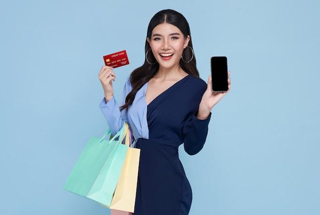 Счастливые красивые азиатские женщины показывая кредитную карту и смартфон и держа хозяйственные сумки изолированные на голубой предпосылке.