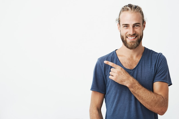 Happy beautiful bearded guy with good-looking hairstyle, smiling and pointing at copyspace