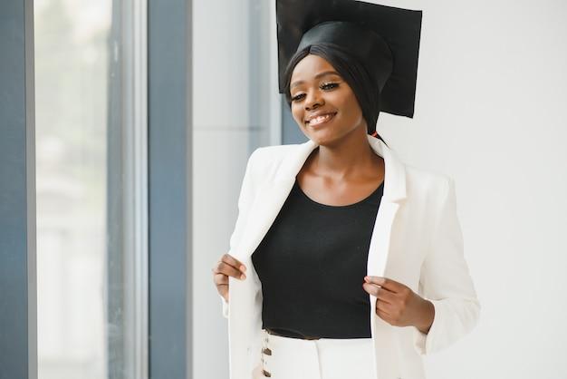 Счастливая красивая черная афро-американская девушка в шляпе выпускников Premium Фотографии