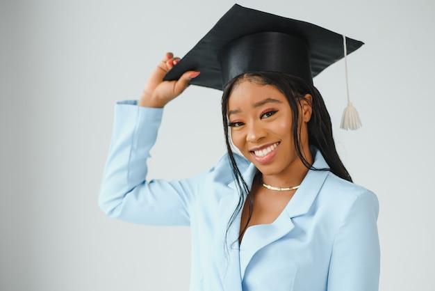 Счастливая красивая черная афро-американская девушка в шляпе выпускников