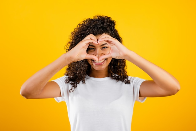 Happy beautiful black girl showing heart with hands isolated over yellow