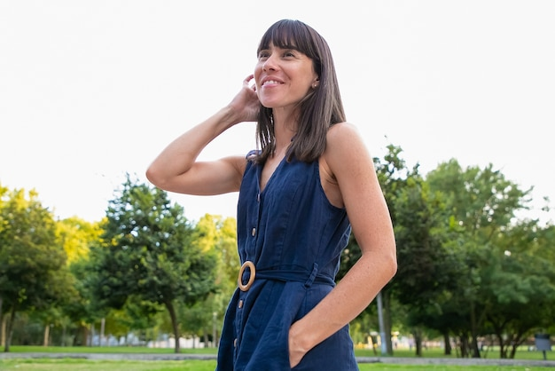 행복 한 아름 다운 검은 머리 여자 도시 공원에 서 서 멀리보고 웃 고. 여름에 야외에서 여가 시간을 즐기는 아가씨. 중간 샷, 낮은 각도. 여성 초상화 개념