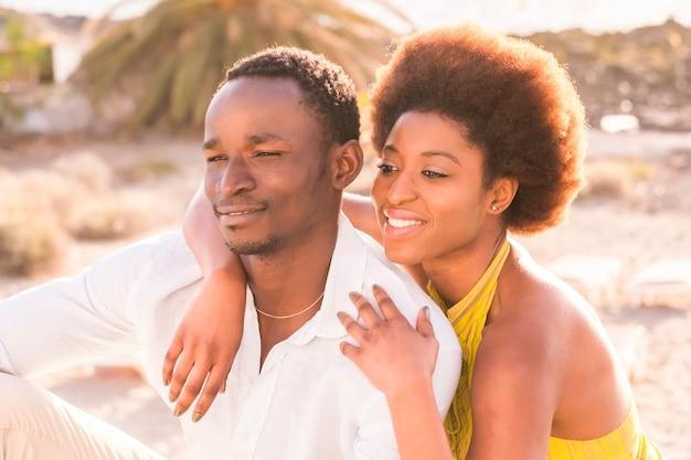恋や友情を持った幸せな美しい黒人人種のアフリカ人夫婦は、夏の休暇や都市でのライフスタイルの下で、大きな笑顔で抱き合って一緒に歩き続ける
