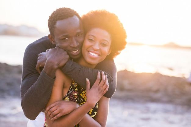 愛や友情の幸せな美しい黒人種アフリカのカップルは抱きしめて一緒に歩いて滞在します