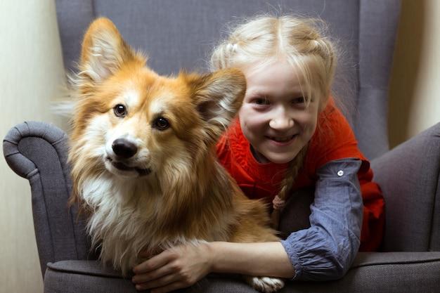 행복 - 아름다운 금발 소녀와 개 코기가 푹신한 카메라를 위해 포즈를 취하는 재미가 있습니다