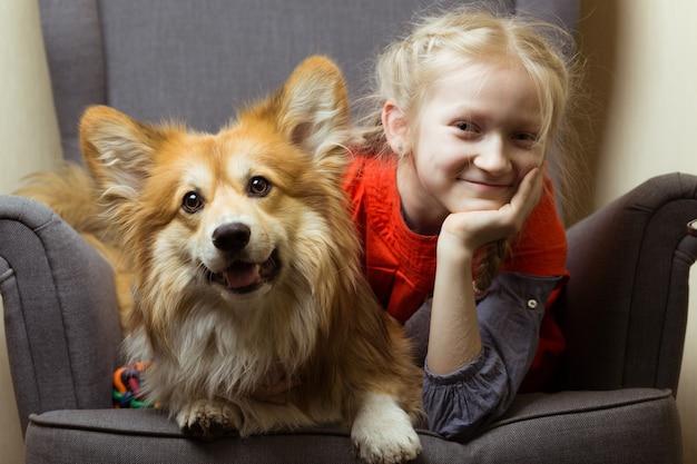幸せ-美しいブロンドの女の子と犬のコーギーふわふわは、カメラのポーズを楽しんでいます