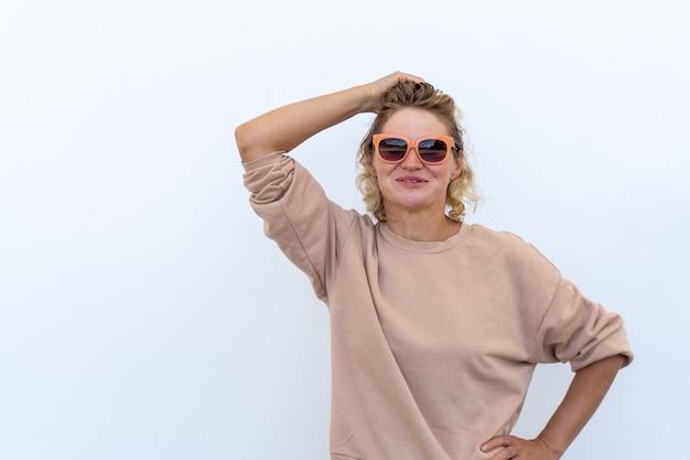 Счастливая красивая белокурая кавказская женщина в очках смеется, глядя в камеру. женщина в солнечный день.