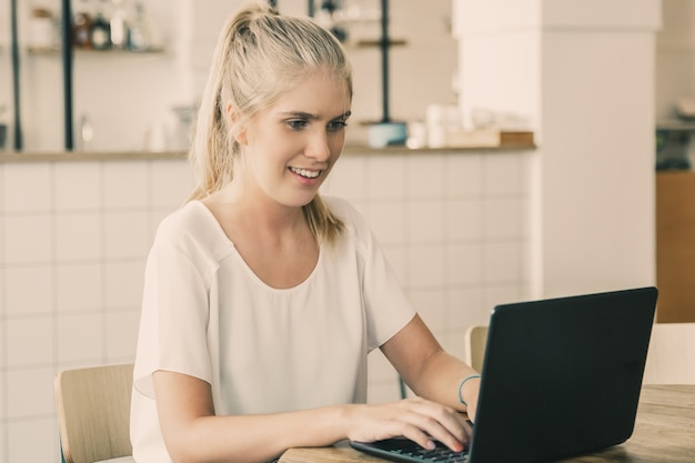Happy beautiful blonde woman sitting at table in co-working space, using laptop, looking at display and smiling