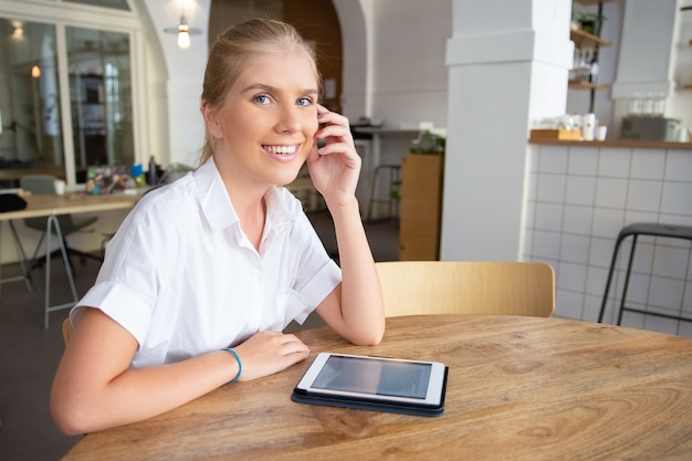 Happy beautiful blonde woman with tablet sitting at table in co-working space,