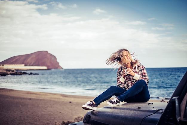 幸せな美しい金髪の若い女の子が屋外に滞在し、オフロードの黒い車で天気と旅行を楽しむ