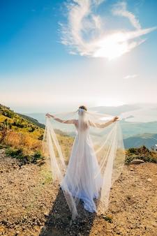 屋外のウェディング ドレスをなびかせて幸せな美しい花嫁