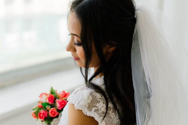 Happy beautiful bride with her veil smiling and excited in interior, wedding morning
