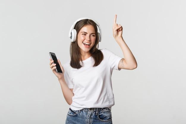 Счастливая красивая девушка брюнет танцует и слушает музыку в беспроводных наушниках, держа смартфон.