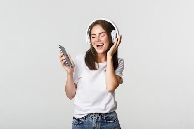 Happy beautiful brunette girl dancing and listening music in wireless headphones, holding smartphone.
