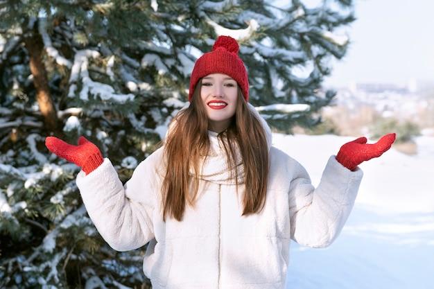 Счастливая красивая девушка брюнет в красной шляпе с бубоном в снежном лесу.