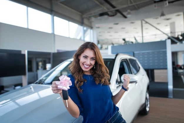 Happy beautiful brunette woman holding car keys in front of new vehicle in automobile dealership showroom
