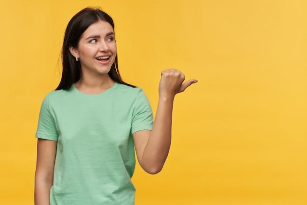 민트 tshirt에서 행복 한 아름 다운 갈색 머리 젊은 여자를 찾고 노란색 벽 위에 절연 엄지 손가락으로 멀리 가리키는