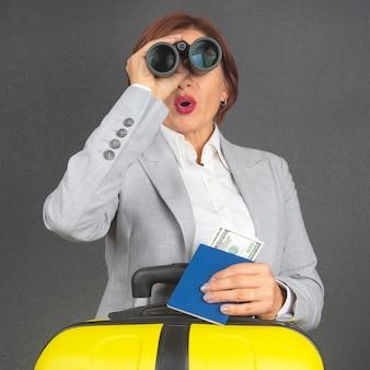 행복 한 아름 다운 비즈니스 여자는 그녀의 여행을 향해 놀람에 쌍안경으로 보인다.