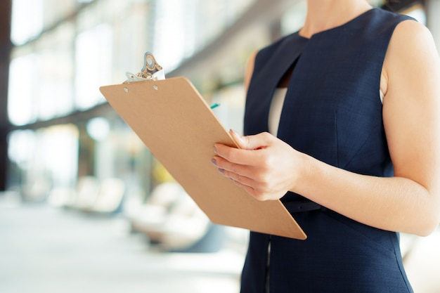 Happy beautiful business woman with clipboard in the office,
