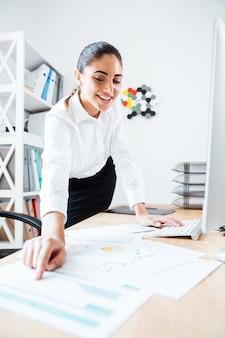 Счастливый красивая бизнесвумен, указывая пальцем на графический отчет, лежащий на столе в офисе