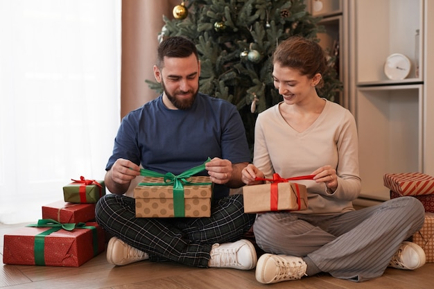 Happy beautiful caucasian couple in homewear sitting with crossed legs near christmas tree and unwra...