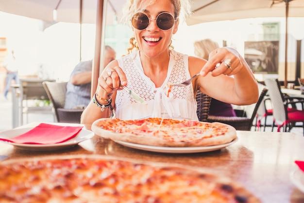 야외에 앉아 레스토랑 피자 가게에서 큰 이탈리아 맛있는 피자를 즐기는 행복 아름다운 백인 아가씨