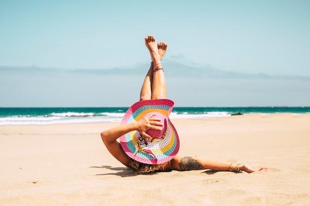 Счастливая красивая кавказская женщина с розовой большой шляпой наслаждается пляжем и отдыхом на летних каникулах в океане, легла на белый желтый песок и взяла шляпу на ветер