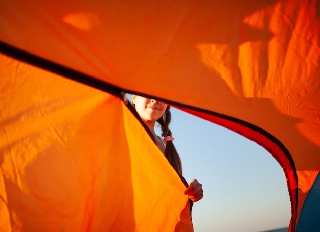 행복하고 쾌활한 어린 소녀는 푸른 바다의 모래 사장에 있는 밝은 텐트 근처에 서서 카메라를 보며 웃는다
