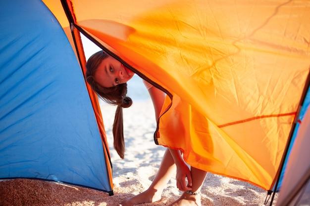 행복 한 아름 다운 쾌활 한 어린 소녀는 푸른 바다의 모래 사장에 밝은 텐트 근처에 서서 카메라를보고 미소