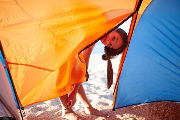 Счастливая красивая жизнерадостная молодая девушка стоит возле яркой палатки на песчаном берегу синего моря и улыбается, глядя в камеру