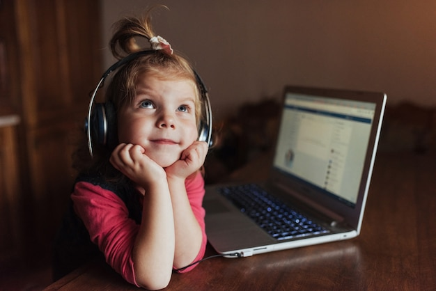 Happy beautiful child in headphones listening to music.