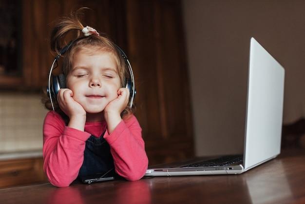 Happy beautiful child in headphones listening to music