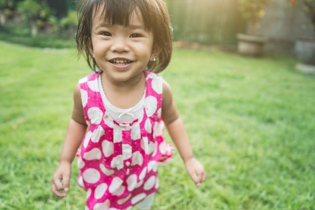 Выражение счастливого красивого ребенка на заднем дворе дома