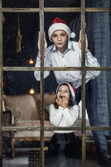 Happy beautiful children boy and girl look out the window at christmas together at home