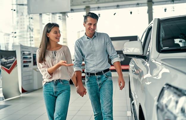 Счастливая красивая пара выбирает новую машину в автосалоне.