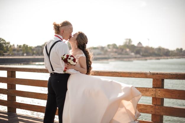 호수에 목재 부두에 키스 행복 한 아름 다운 커플. 결혼식의 개념