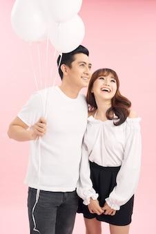 お互いを見て、風船を持って幸せな美しいカップル