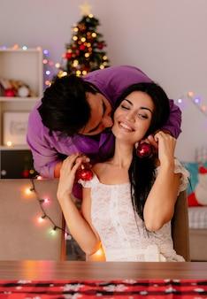 Felice e bella coppia uomo che appende le palle di natale sulle orecchie della sua ragazza che si diverte nella stanza decorata di natale con l'albero di natale nel muro